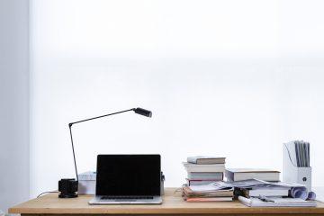 Schreibtisch mit Bücher, Lampe und Laptop
